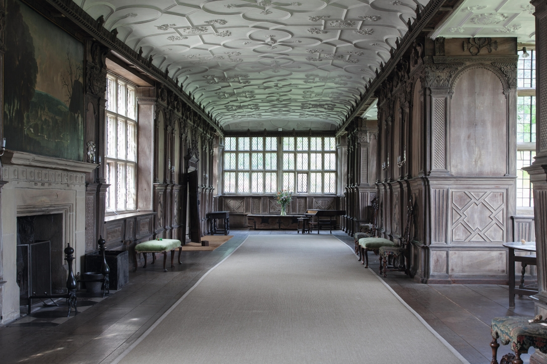 Haddon Hall.  The Long Gallery. A union of natural surfaces; wood, stone and plaster with no colour, creating a dry beauty. Rex Whistler's painting, a romantic vision of the house in its landscape is on the left above the fireplace.