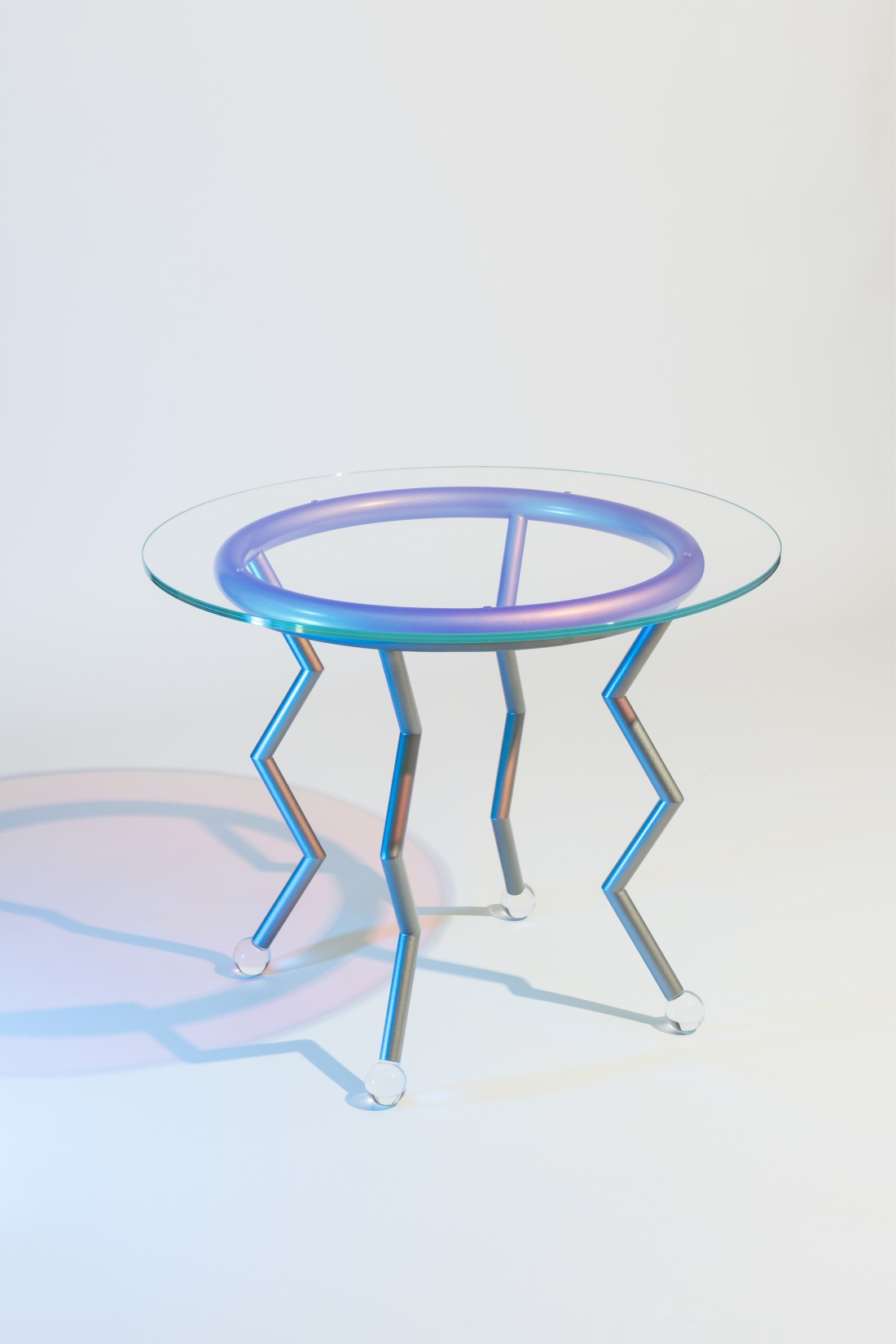 "Medusa, Masanori Umeda, 2020 (based on a 1982 design), limited edition of 24 items + 1 artist's proof, ""Night Tales"" Collection, Post Design. Table with pale blue metal base, iridescent, dichroic glass top and round plexiglass feet. Dimensions: diameter 90, H 71.5 cm. Photograph © Delfino Sisto Legnani. Courtesy of Memphis srl."
