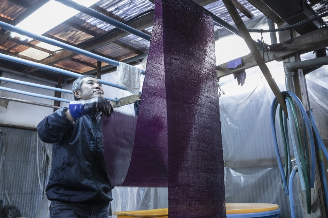 OGAWA Koji dyer at Yoshioka Dyeing Workshop hangs dyed textiles - see Living Colours exhibition 5 April-19 May at Japan House